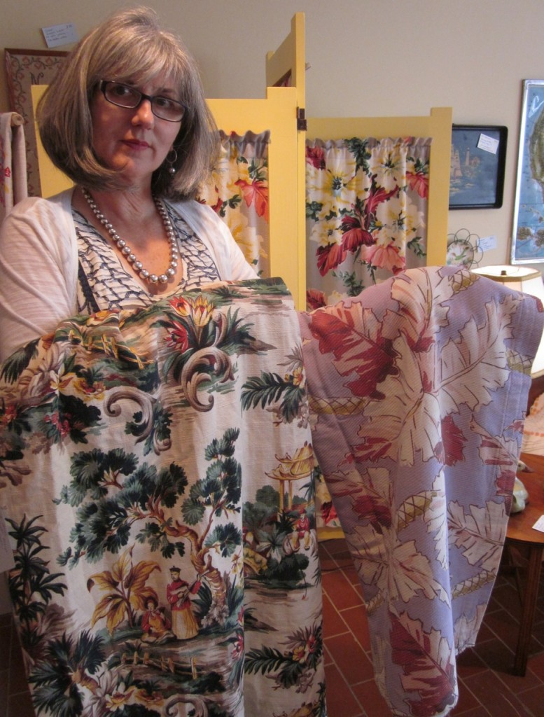 Holding up some vintage barkcloth pieces in front of a three-panelled screen with vintage barkcloth as well.