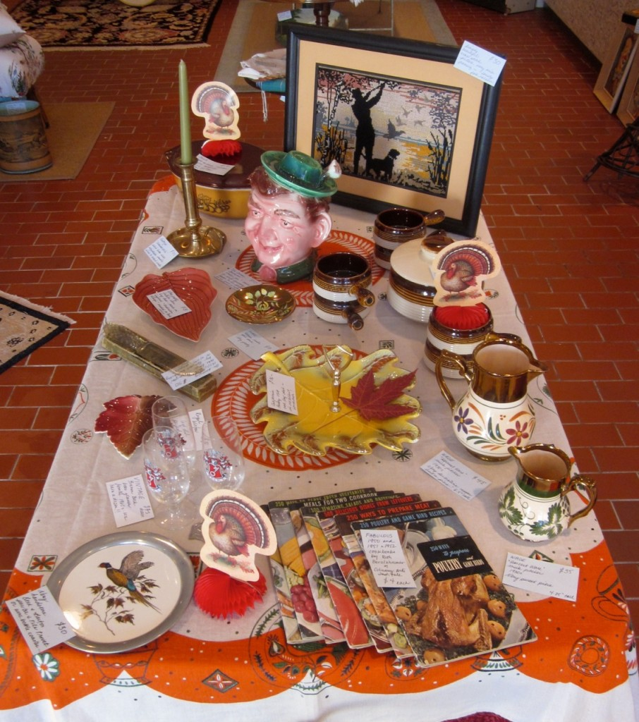 "Harvest table ideas Hunting cross-stitch ($30), German gentleman cookie jar ($50), Pyrex ""old orchard"" covered dish ($30). Luster jugs ($45/$35), chamberstick candleholder ($35). Large leaf dish with handle ($36), Royal Winton leaf dish ($30), Carleton Ware leaf dish ($18). Pheasant pewter trivet ($30), copper lustre dish ($18), 12 Beck's beer glasses ($75)."