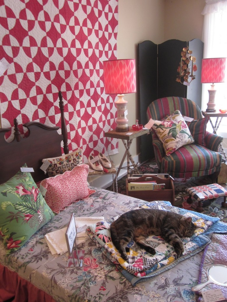 Red quilt $125 Pair of pink lamps $195/pair Green barkcloth cushion $85 Patch quilt $200 Striped armchair $175